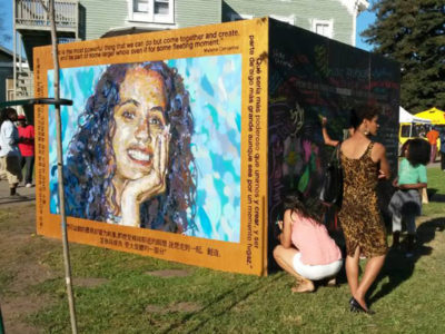 Visitors at Life is Living contribute to the chalk wall adjoining Melanie Cervantes' portrait, Oakland, CA, October 11, 2014.