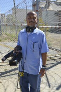Brian Asey with video camera in the San Quentin yard. Photo by Nigel Poor.