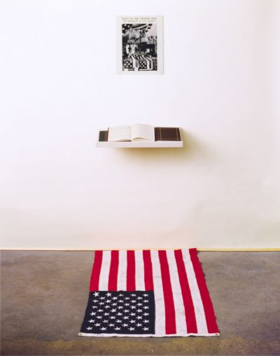 What is the Proper Way to Display a U.S. Flag? Installation: Silver gelatin print, books, pens, shelf, active audience, US flag, 80 x 28 x 12 in., 1988.