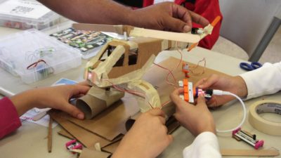 A family collaborates on a helicopter made with electronic components and cardboard at The Plug-In Studio ArtMakerSpace at ElevArte Community Studio. Photo by Kerry Richardson.