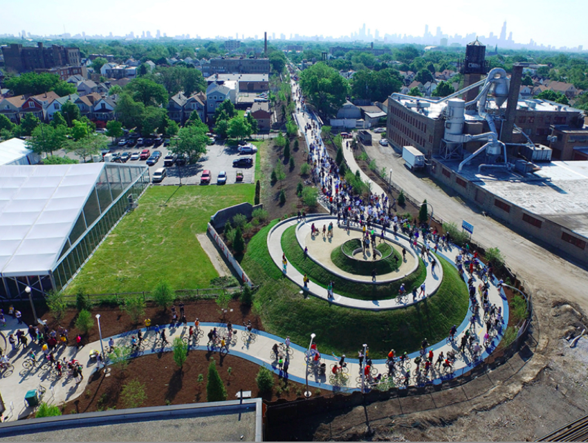 Opening day bike parade at the west end Observatory of The 606, Chicago, 2015. Created from trail construction soils, the spiraling seasonal earthwork re-grounds audiences in their geographic and cultural reality. Image: The Trust for Public Land
