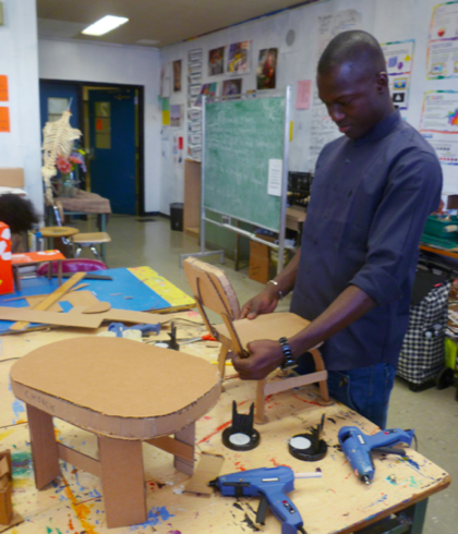 African (Mali) American student, designing culturally relevant furniture from found cardboard boxes for a Funktional Design Class conducted by Xenobia Bailey at Boys & Girls High School as part of Funk, God, Jazz and Medicine: Black Radical Brooklyn, sponsored by Creative Time, Summer 2014. Photo: Xenobia Bailey