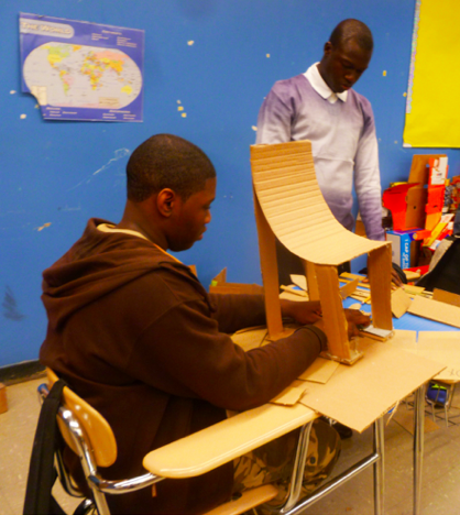 African (Bed-Stuy, Brooklyn) American student, designing culturally relevant furniture from found cardboard boxes for a Funktional Design Class conducted by Xenobia Bailey at Boys & Girls High School as part of Funk, God, Jazz and Medicine: Black Radical Brooklyn, sponsored by Creative Time, Summer 2014. Photo: Xenobia Bailey