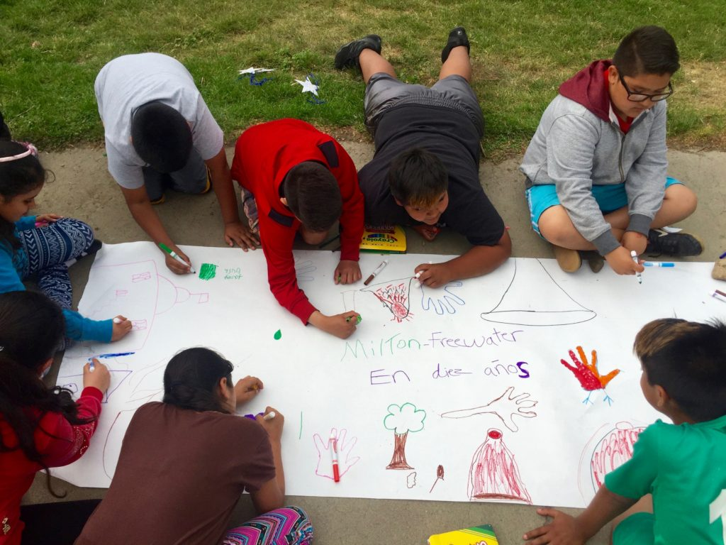Young people in a migrant housing community draw the future of Milton-Freewater, a farming community in eastern Oregon. From MILTON, a co-production with Ashley Sparks and Pearl Damour. Courtesy the artist.