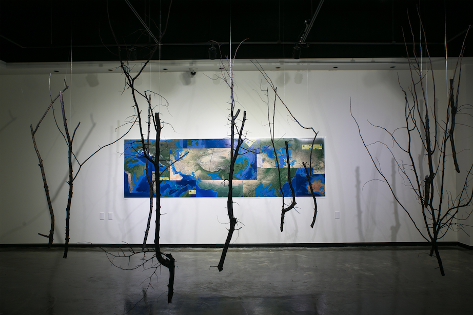 Detail of an installation for the Carbon Art Project curated by Yu Hyun-Ju at the Korea Research Institute of Chemical Technology (KRICT) Art Gallery, Daejeon, South Korea. Photo by Aviva Rahmani. 10'x15' Photomontage with suspended, ultramarine blue painted quince branches illustrating sea level rise when all Arctic and Antarctic ice melts, and some remaining refugia for terrestrial life. Photo: Aviva Rahmani, 2017