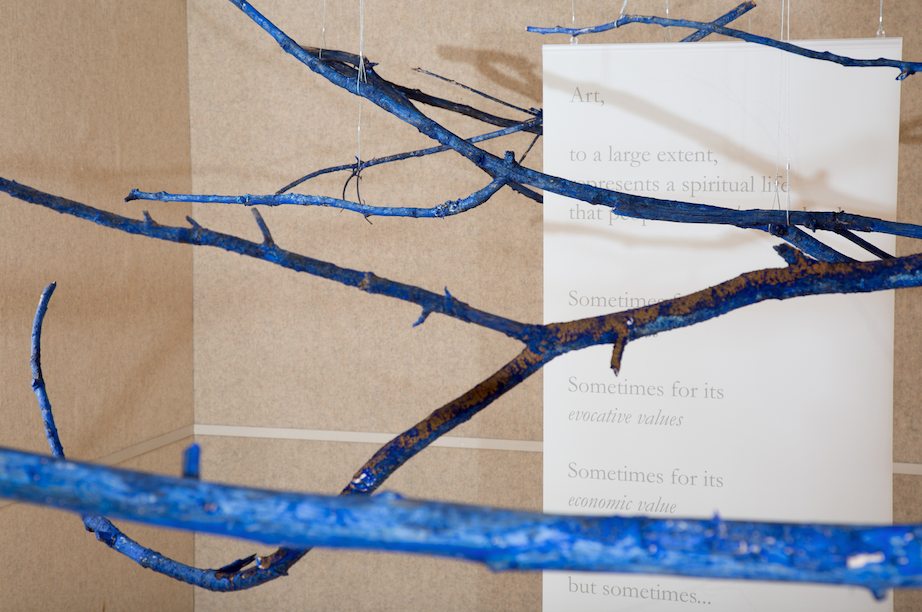 "Branches painted with a casein of buttermilk and ultramarine blue pigment with 10- 60"" x 36"" hanging translucent panels printed with text excerpted from writings by the artist and hung from gallery ceiling. This installation, at the Perspective Gallery of Virginia Tech, was the setting of a performed recitation of the legal premises as a chorale. Photo: Sarah Miller, 2016"