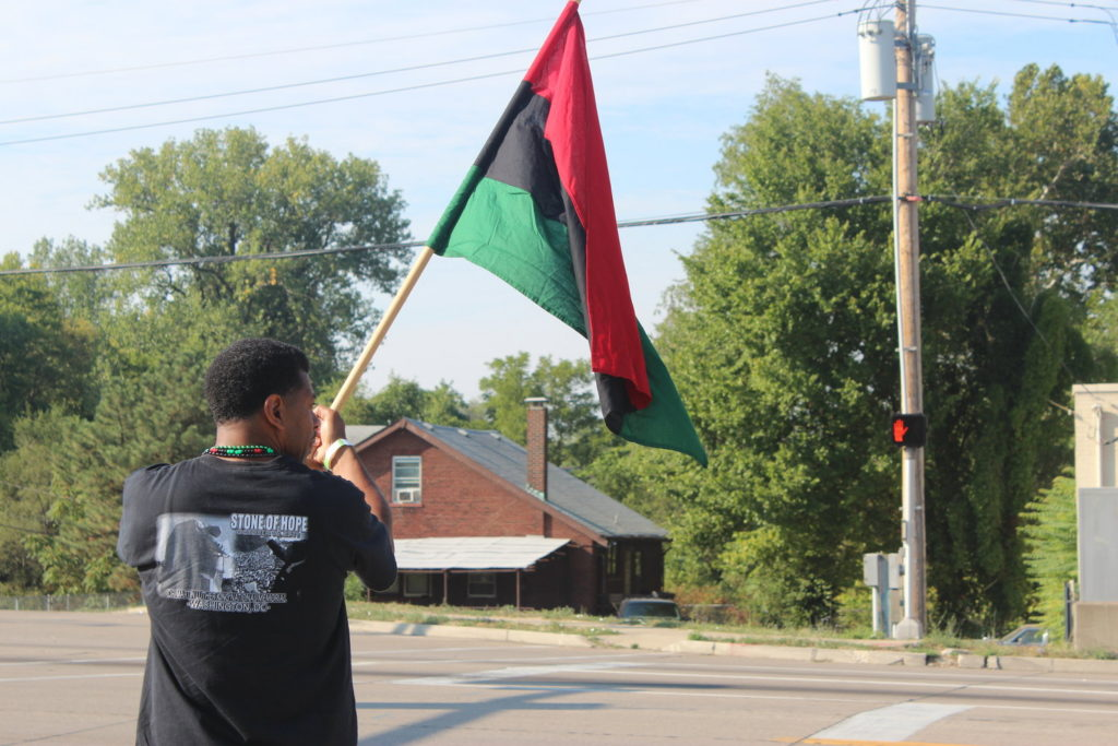 After participating in the premiere Martin Luther King Legacy Walk for St. Louis co-organized by Freeman Word, a man demonstrates Pan-African pride by waving a red, black, and green flag in the streets of St. Louis. The concept of unity among people is a founding principle of the Zakatu Madrasa, which plans to use the Nguzo Saba as its guiding principles. Photo: Luke Terrell