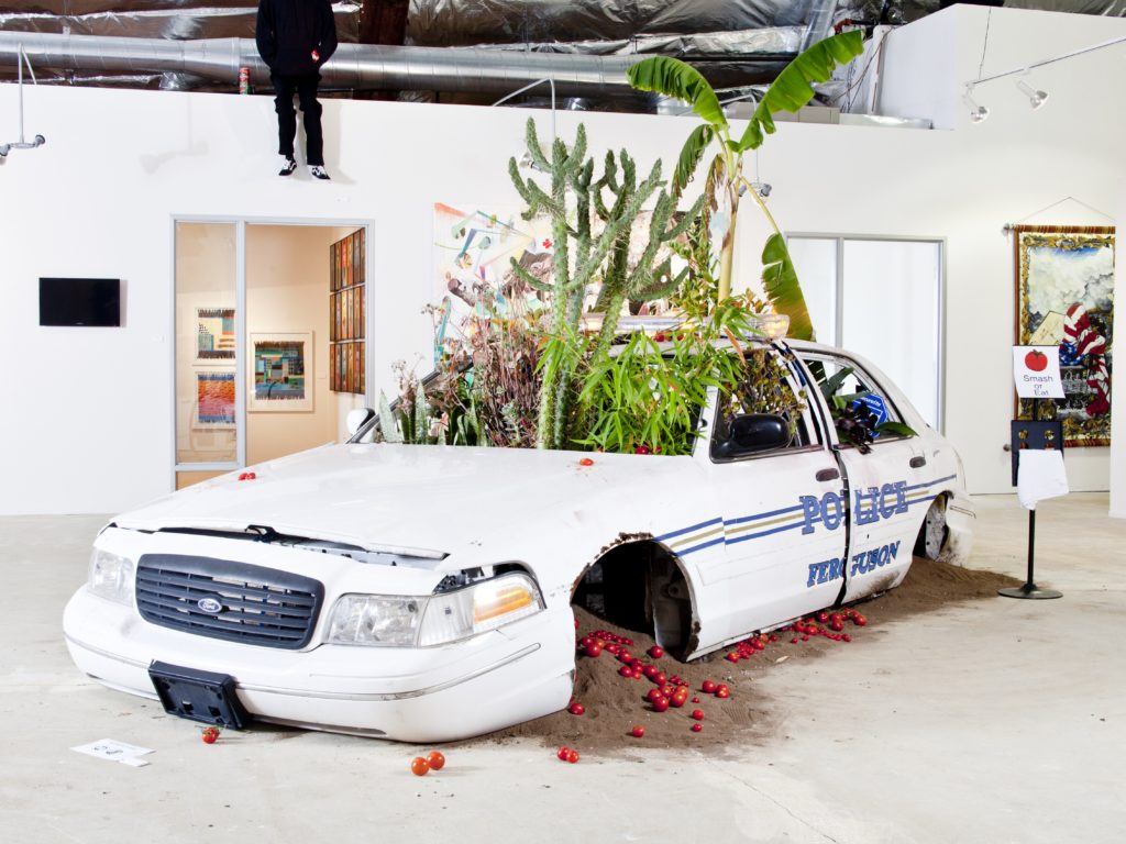 American Dreamers Phase 2 (police vehicle, earth from Ferguson, various fruit trees and plants). Image courtesy the artist.