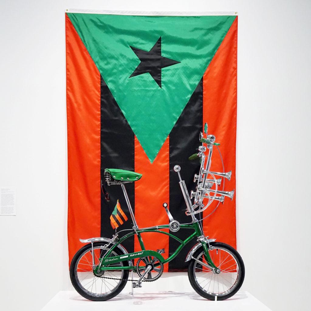 "RUN-A-BOUT,20171969 Schwinn Run-A-Bout, chrome machete, flags48"" x 60"" x 26."" Puerto Rican Flag in Red, Black and Green, 201796"" x 60."" Courtesy the artist."