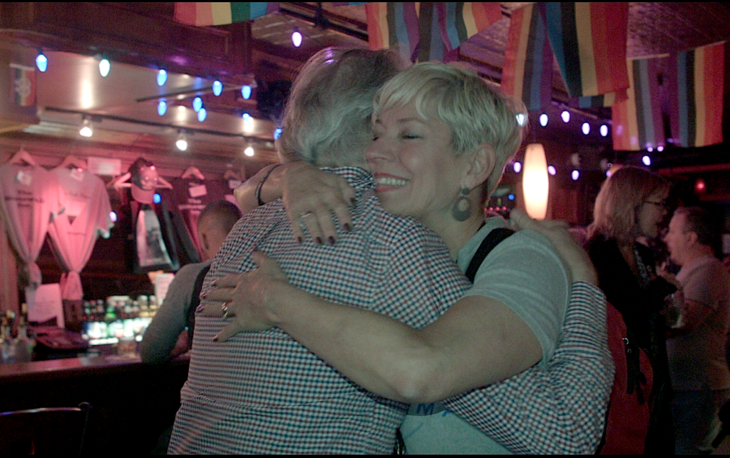 Sara gives out free hugs at Stonewall Inn at the end of the first Free Mom Hugs Tour, photo courtesy the artist.