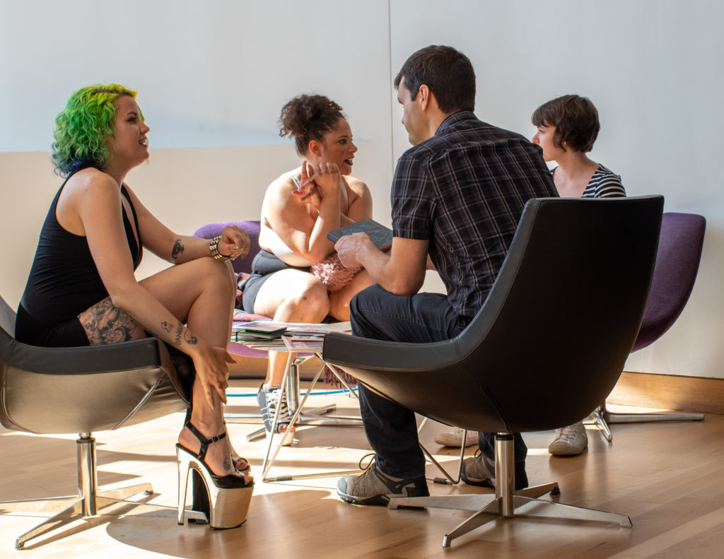 Visitors choose from a menu of topics to discuss one-on-one with dancers at a Feminist Strip Club event. Photo: Boris Oicherman.
