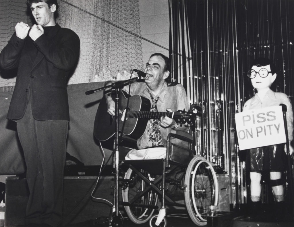 """: Ian Stanton, a leading singer and songwriter in the Disability Arts Movement in the United Kingdom, performs onstage next to a BSL interpreter and """"Chip the Crip,"""" a vintage Spastics Society collection box. Image courtesy of the National Disability Arts Collection and Archive (NDACA)."""