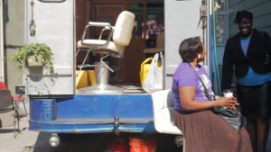Exterior of the mobile salon with volunteer stylists Carol Thomas and Nahomie Marcena of Just Because Hair Therapy, New York, NY, 2014.