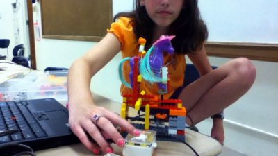 A participant demonstrates her programmed and motorized automaton in The Plug-In Studio Interactive Art + Tech Lab at the Center for Gifted. Photo by Steve Ciampaglia.