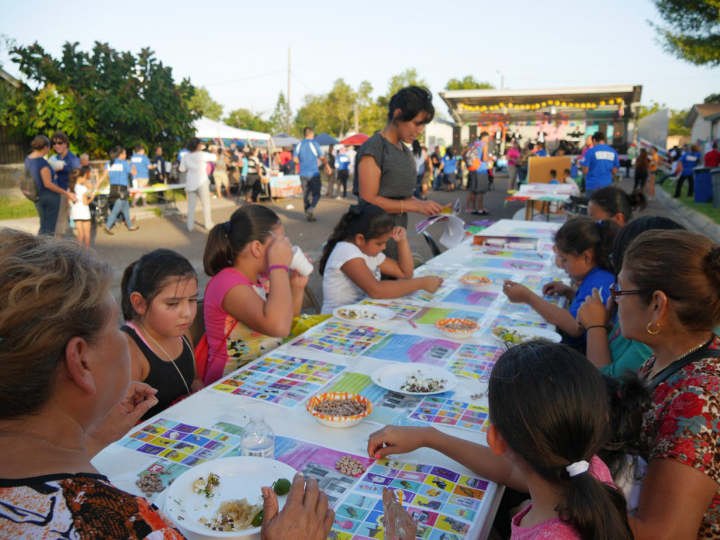 Brownsville Lóteria, 2016. Participants playing Brownsville Lóteria (Mexican Bingo) and making their cards for play. The game substituted iconic Lóteria imagery with images specific to the region, placing a heavy emphasis on civic art. Attendees were also invited to make their own cards by reflecting on the images, places and things that they think define the city. Participant responses ranged from memorable water fountains to their personal living room. Project concept developed as part of Activating Vacancy Arts Incubator in collaboration with buildingcommunityWORKSHOP. Image: buildingcommunityWORKSHOP.