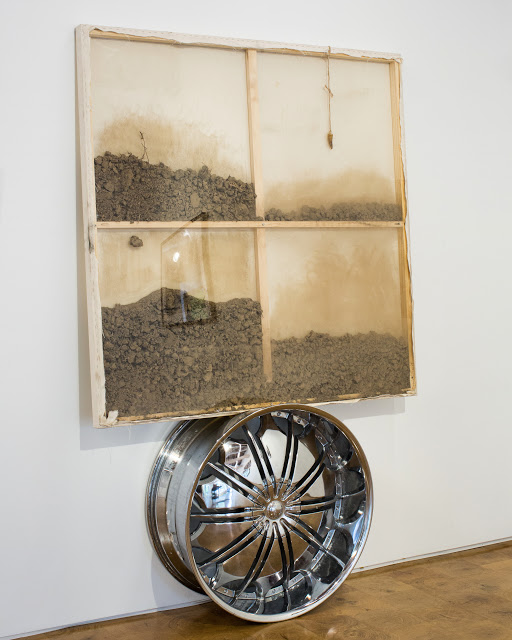 38° 44′ 18.49″ N, 90° 16′ 25.93″ W (Giganotosaurus tooth, soil from Palestine, Malcolm X's birthplace, Ferguson Missouri, alloy wheel, canvas). Image courtesy the artist.