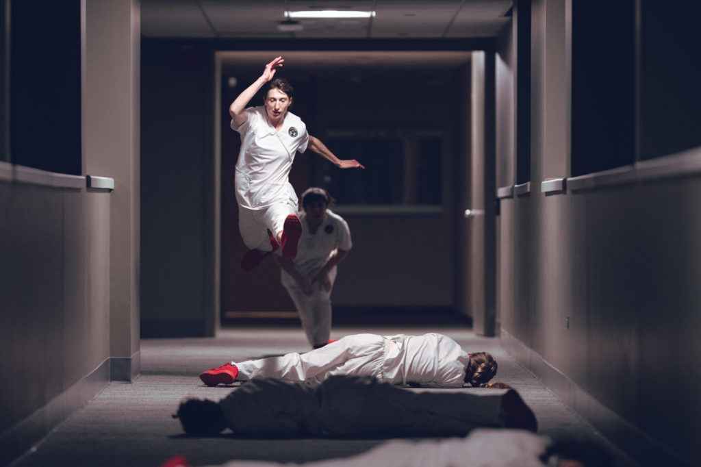 First, Do No Harm Bridge Dance: Performer Tara Rynders running through the halls exploring the exhaustion, grief, and compassion fatigue that arises in the complicated roles nurses play with patients, doctors and other nurses. Photo by DW Burnett.