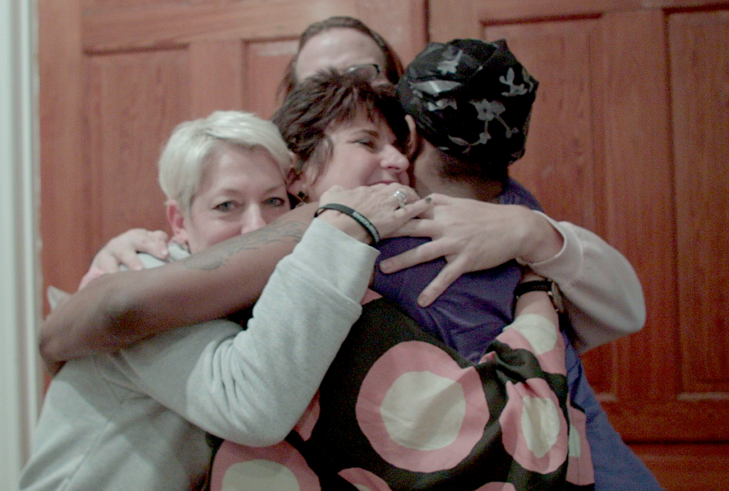 Mama bears Sara Cunningham, Laura Beth Taylor and Susan Cottrell share a hug with a resident of Philadelphia's Home for Hope shelter for LGBTQ people, photo courtesy the artist.