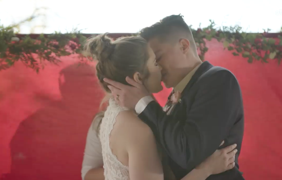 "Marlee & Tabatha Castillo share a kiss at their wedding where Sara Cunningham served as a ""stand-in mom"" for Tabatha, photo courtesy the artist."