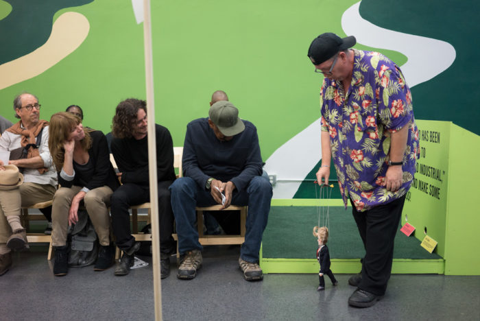"Larry Swanson performs at Los Angeles Poverty Department's ""The Back 9"" exhibition at the Skid Row History Museum and Archive, 2017. Photo by Linus Shetu © Los Angeles Poverty Department."