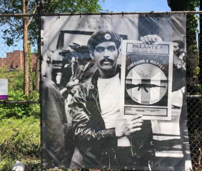 Young Lords member with Pa'lante Newspaper, 1970. Photo by Hiram Maristany, installation by Miguel Luciano.