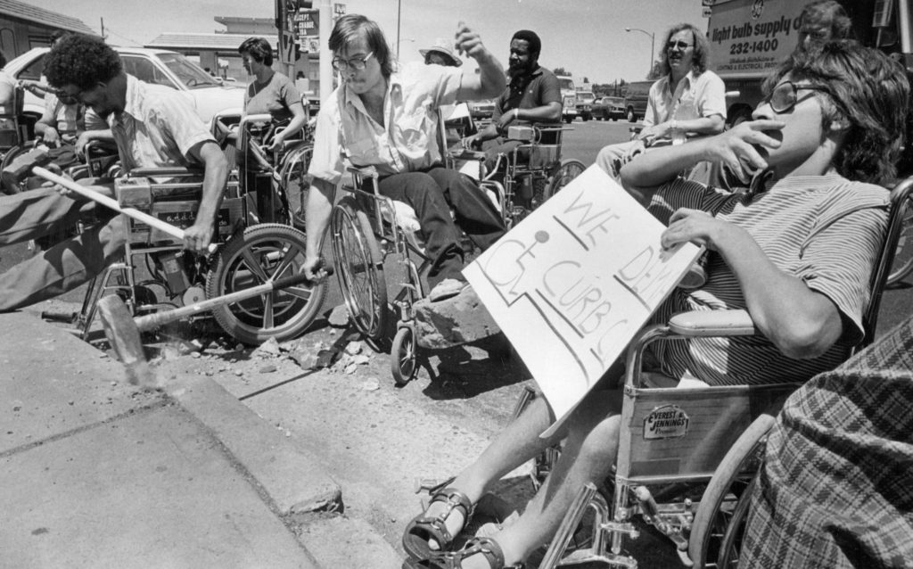 Disability rights activists gather to bludgeon a curb on July 1, 1980 during a demonstration against obstacles to their mobility.