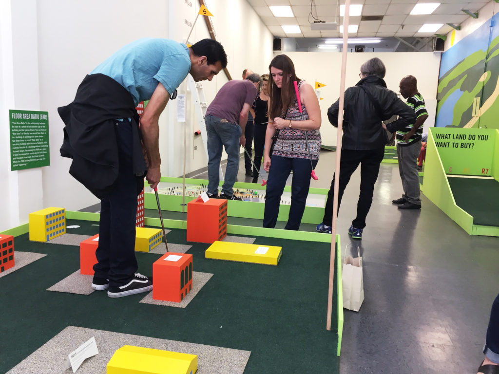 Participants engaging with The Back 9 installation by artist Rosten Woo at the Skid Row History Museum and Archive in 2017. Image courtesy of Los Angeles Poverty Department.