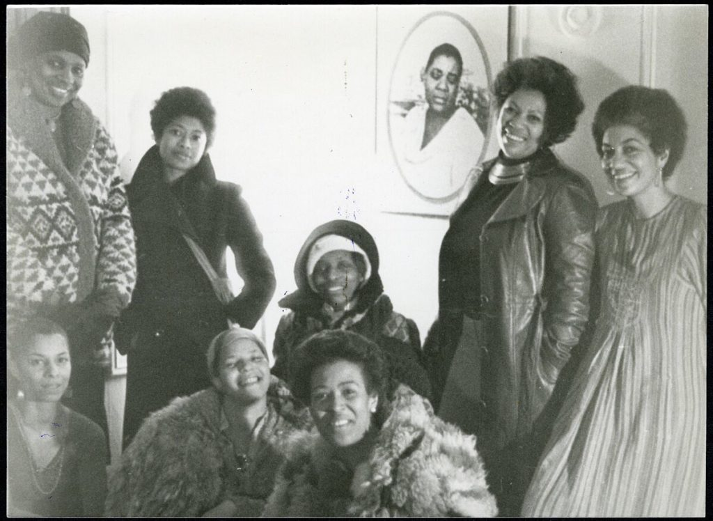 Members of The Sisterhood, 1977, a writing collective/circle founded by Alice Walker and June Jordan in NYC. Front row, left to right: Nana Maynard, Ntozake Shange, Louise Meriwether; back row, left to right: Vertamae Smart-Grosvenor, Alice Walker, Audrey Edwards, Toni Morrison and June Jordan. Image courtesy of Emory University's Stuart A. Rose Manuscript, Archives and Rare Book Library.
