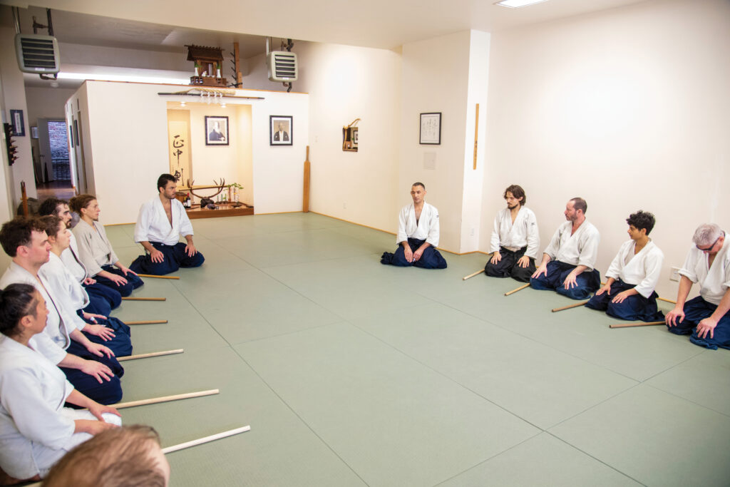 Aikido students gather in a circle to thank one another for training at the end of each class. Photo by Lorenzo Tijerina.