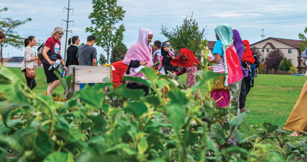 Community members tour the community garden at World Garden Commons, the pilot site of The Fargo Project, tended by Growing Together during the Welcoming Week celebrations.