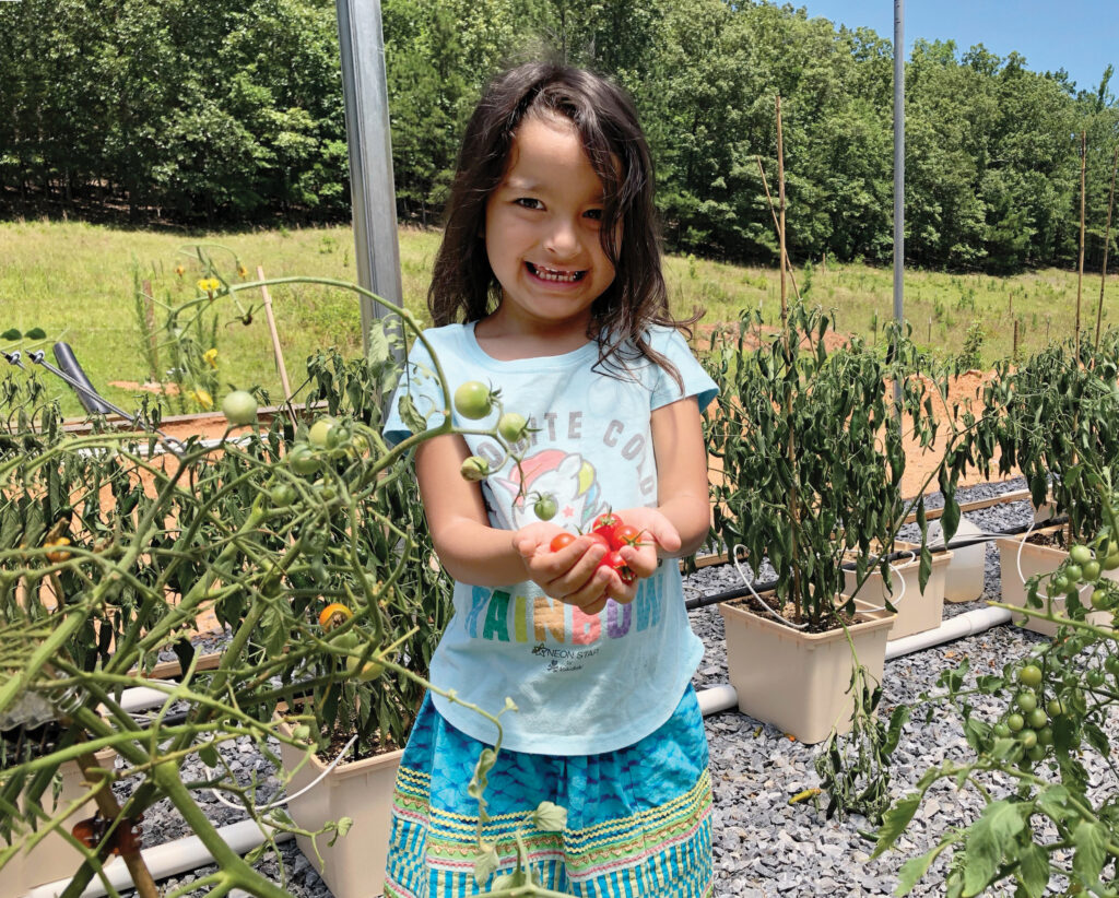 A Maskoke child holds tomatoes grown in the Ecovillage greenhouses. Residents grow vegetables based on the traditional diets of their ancestors.